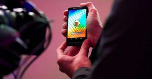 A man holds a Motorola RAZRi smartphone with an Intel processor during the launch of the device on September 18, 2012