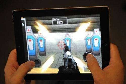 """A man plays the National Rifle Association (NRA) iPhone/iPad app, """"NRA: Practice Range"""" on January 15, 2012"""