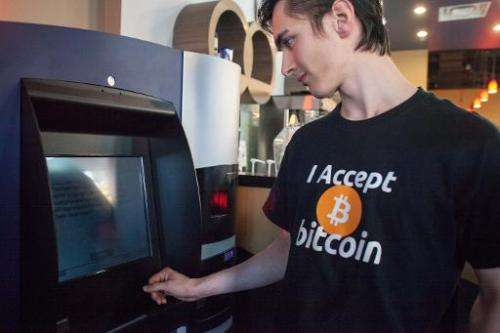 A man uses the world's first bitcoin ATM on October 29, 2013 at Waves Coffee House in Vancouver, British Columbia