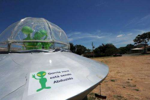 """A mock UFO with a sign reading """"Smile, you are being abducted"""" is pictured north of Brasilia, in December last year"""