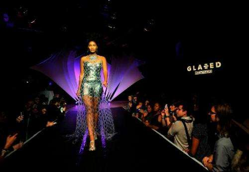 A model struts down a runway wearing a dress made from plastic rings at the Glazed Conference in San Francisco, California on Se