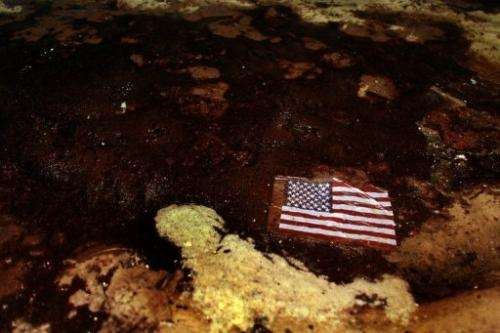 An American flag lays in oil that washed ashore from the Deepwater Horizon oil spill on July 4, 2010 in Alabama
