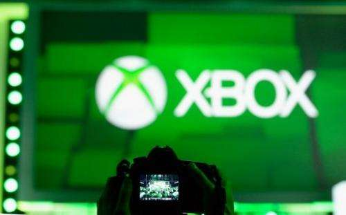 An attendee takes a photo of the Xbox logo during a Microsoft Xbox news conference on June 10, 2013, in Los Angeles