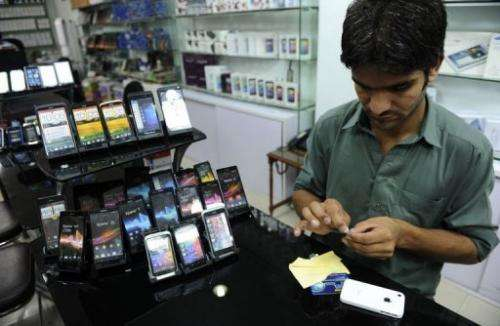 An employee pastes a screen protector onto a mobile phone at a shop in Islamabad on August 6, 2013