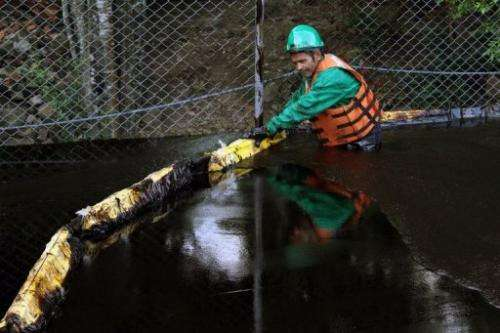 An employee places a barrier following an oil spill from a pipeline, in Chinacota, December 11, 2011