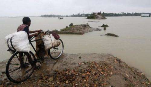 An Indian villager looks across a road that was washed away by floods at Burgaon Patekibori village, on October 9, 2012
