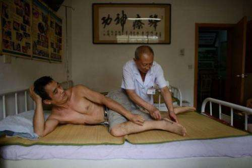 A patient receives a bee sting administered by a doctor of traditional Chinese medicine on August 2, 2013