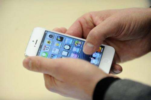 A person examines an iPhone 5 at an Apple store in Saint-Herblain, western France, on November 15, 2012