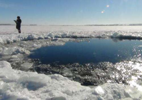 A police officer stands near a six-metre hole in the ice of a frozen lake, reportedly the site of a meteor fall, outside the tow