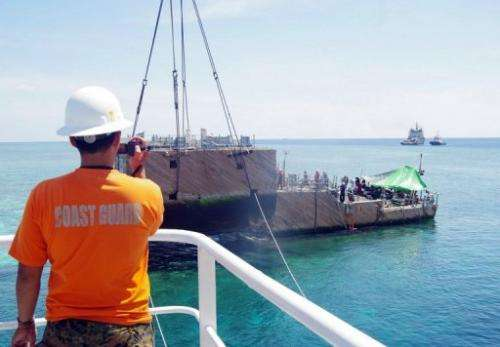 A portion of the stern of the USS Guardian is being lifted by a boat crane, off Palawan island, on March 30, 2013