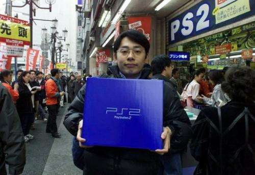 A student holds his newly bought Sony's PlayStation 2 video game console, in Tokyo, on March 4, 2000