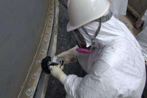 A TEPCO worker check contamination around a contamination water tank at Fukushima on September 4, 2013
