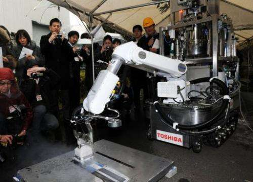 A Toshiba decontamination robot is demonstrated at Toshiba's technical center in Yokohama on February 15, 2013