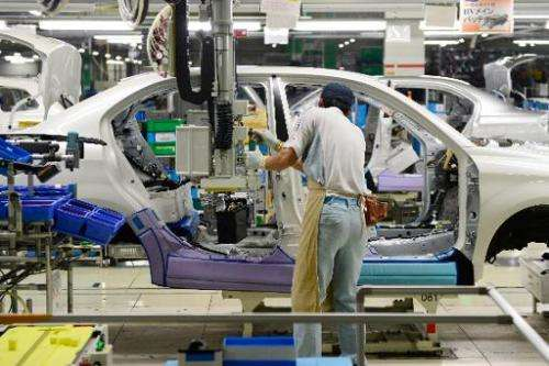 A Toyota Motor employee fixes the main battery of the hybrid system on an assembly line for the Corolla Axio at a plant of the c