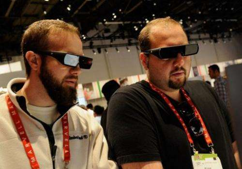 Attendees of a technology convention wear 3D glasses in the a booth during on January 11, 2012 in Las Vegas, Nevada