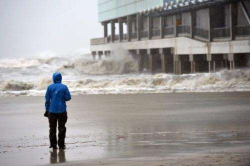 A TV reporter watches waves hit a pier before the arrival of Hurricane Sandy on October 29, 2012 in Atlantic City