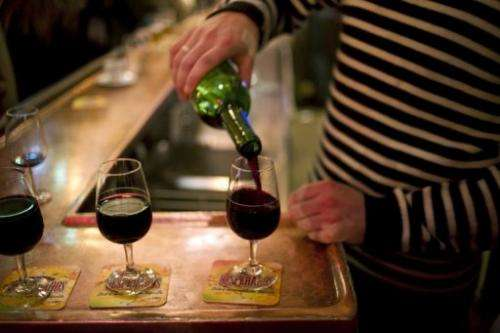 A waiter serves glasses of red wine at the counter of a bar in Paris on December 2, 2011