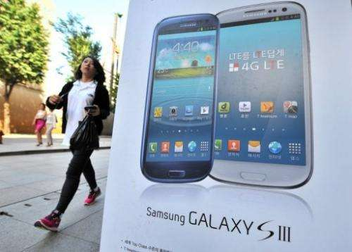 A woman walks past an advertisement for the Samsung Galaxy S3 smartphone in Seoul on August 27, 2012