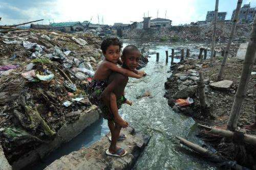 Bangladeshi children prepare to cross a polluted stream near a tannery in the Hazaribagh District of Dhaka on October 6, 2012