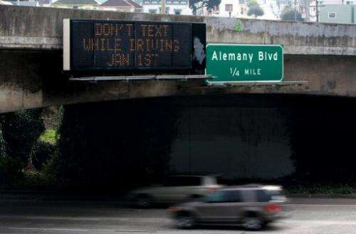 Cars drive by a sign notifying of a new texting while driving law on December 29, 2008 in San Francisco, California