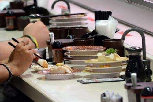 Customers enjoy sushi at the Uobei restaurant in Tokyo, on June 10, 2013