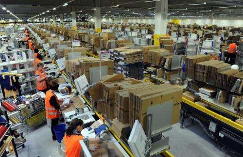 Employees pack parcels at the logistics centre of Amazon in Bad Hersfeld, central Germany, on December 20, 2010