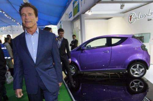 Former Governor of California Arnold Schwarzenegger walks past a Belumbery electric car in Geneva on March 8, 2012