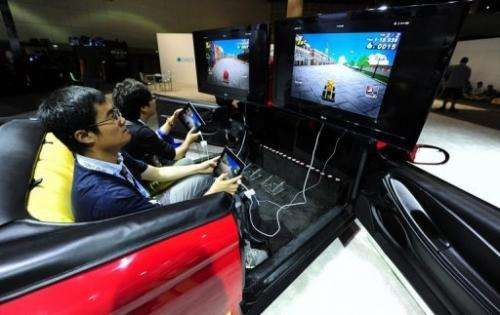 Gamers sit in a car while playing Wacky Motors in a videogame extravaganza in Los Angeles on June 7, 2012 in California