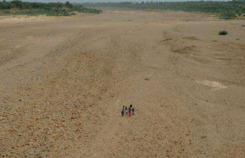 Indian villagers cross the dry bed of the Sabarmati River near Dholakuva village in Gandhinagar, on August 9, 2012
