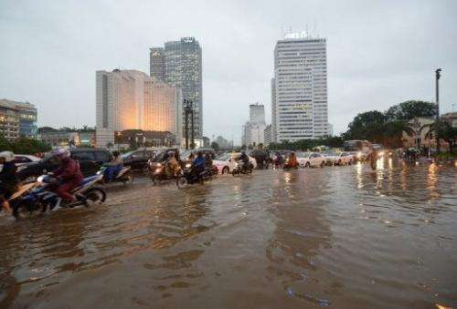 Indonesian motorists manouver through a flooded main street in Jakarta on February 6, 2013
