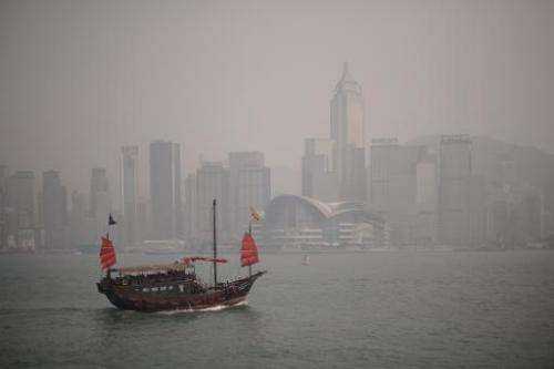 In this file picture taken on April 15, 2013, a junk sails past the Hong Kong skyline which is shrouded in a dense blanket of to