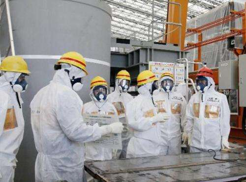 Japan PM Shinzo Abe (right) is briefed about the advanced liquid processing system (ALPS) on a visit to the stricken Fukushima n