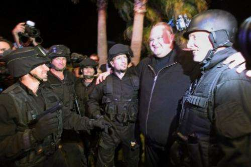 Kim Dotcom (2nd R) poses with actors dressed as police after the launch of his website in Auckland on January 20, 2013