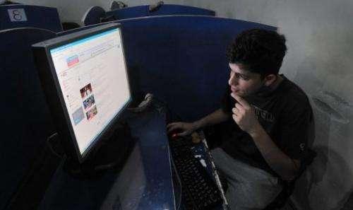 Pakistani student Abdullah Raheem browsing YouTube at a internet cafe in Lahore on September 9, 2013