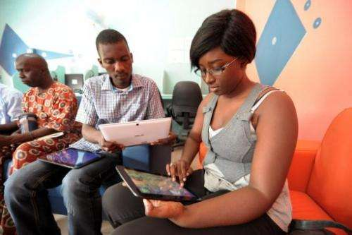 """People browse the Internet using tablets, during the opening of """"Tablette Cafe"""", on May 27, 2013, in Dakar"""