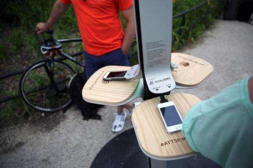 People charge their cell phones at a free solar-powered charging station set up by AT&T at Brooklyn Bridge Park on June 18,