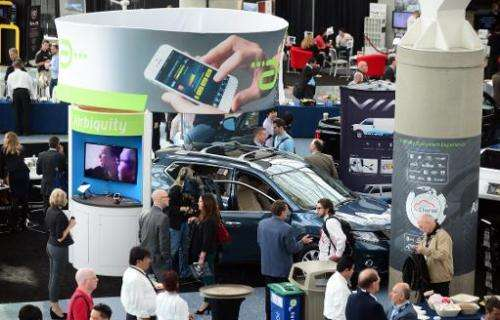 People crowd around a Nissan Rogue loaded with Airbiquity technology on November 19, 2013 in Los Angeles, where the LA Auto Show