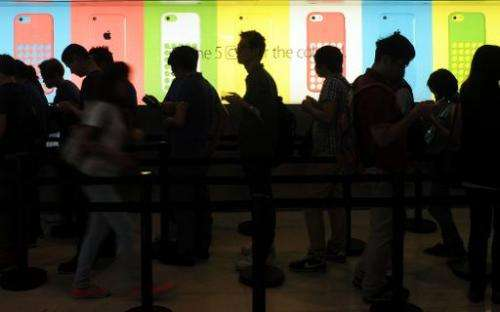 People queue outside an Apple store to purchase the iPhone 5s and 5c in Hong Kong on September 20, 2013