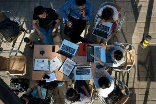 People sit around laptop computers at a cafe in Beijing on May 29, 2013