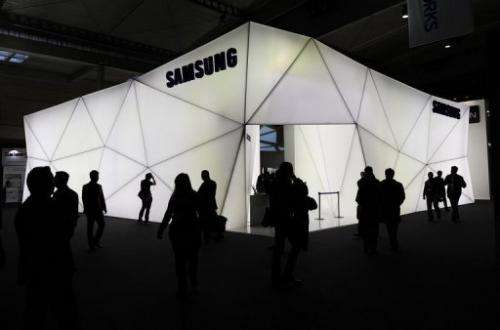 People walk in front of the Samsung stand at the 2013 Mobile World congress in Barcelona on February 25, 2013.