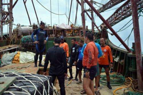 Philippine coast guard personnel inspect the Chinese fishing vessel that ran aground off Tubbataha reef, April 10, 2013