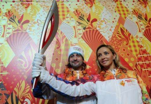 Prominent Russian ice dancers Tatiana Navka (R) and Ilia Averbukh, pose with the Torch in Moscow, on January 14, 2013