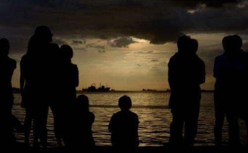 Protesters flock to the water front to watch a cloudy sunset in Manila Bay on February 12, 2013.