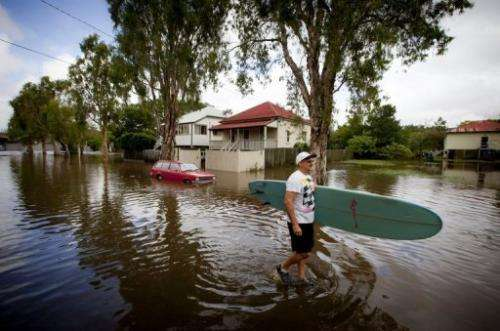 Roger Barnes rescues a friend's surfboard from a flooded home in the Brisbane suburb of Newmarket on January 28, 2013