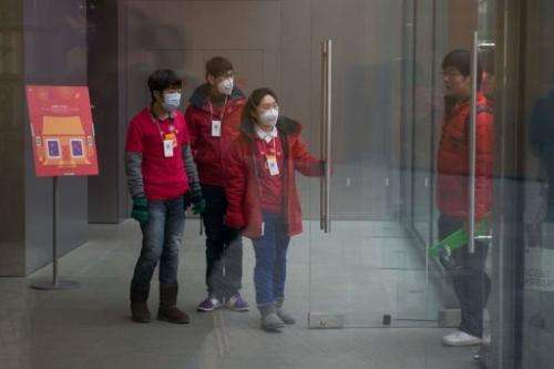 Shop assistants wear face masks as they welcome customers at a store in Beijing, January 29, 2013