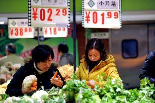 Shoppers buy vegetables at a supermarket in Hefei, east China's Anhui province on December 9, 2012