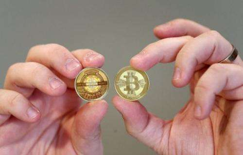 Software engineer Mike Caldwell shows the sides of a physical Bitcoin he minted in his shop on April 26, 2013 in Utah