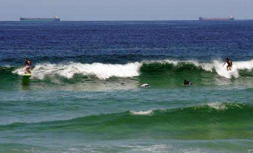 Surfers ride the waves at Redhead Beach near Newcastle on February 23, 2012