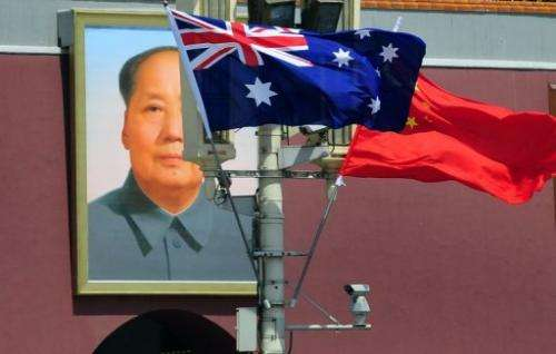 The national flags of Australia and China are displayed before a portrait of Mao Zedong in Beijing in April 2011
