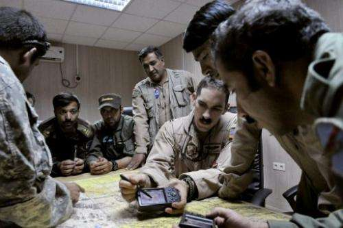 US Air Force Captain Tyler Rennell (3rd right) shows Afghan pilots how to use a GPS in Kandahar on October 11, 2009
